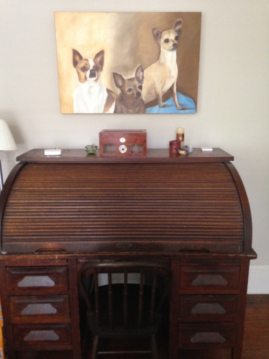A custom painting of three of his dogs hangs over an antique roll desk.